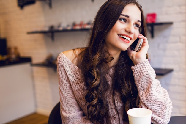 モダンなカフェでスマートフォンで書き込みメッセージを入力する女性。携帯電話を使用してコーヒーやカプチーノのテーブルに座っている若いきれいな女の子の画像をトリミングしました。 無料写真