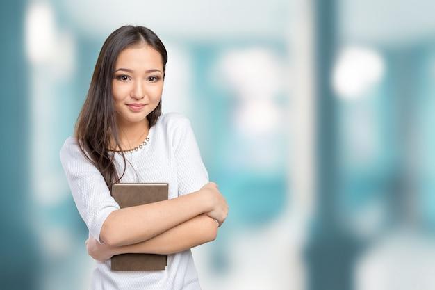 Woman university / college student holding book Premium Photo