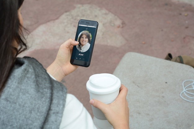 Woman unlocking smartphone with facial recognition technology Premium Photo