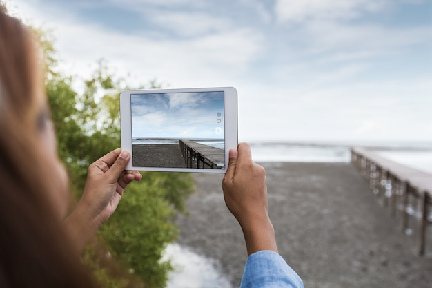 Woman use digital tablet taking landscape photo Premium Photo