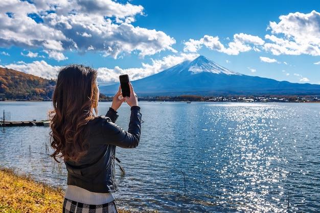 女性が携帯電話を使って、日本の河口湖の富士山で写真を撮ります。 無料写真