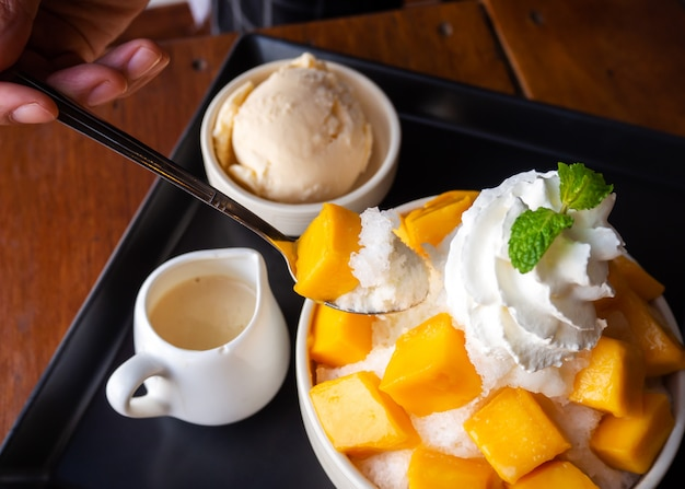 Woman use spoon take shaved ice dessert, served with mango sliced. Premium Photo
