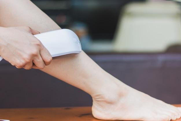 Женщина, использующая личную эпиляцию эпиляции ipl, готовится к уходу за кожей дома Premium Фотографии