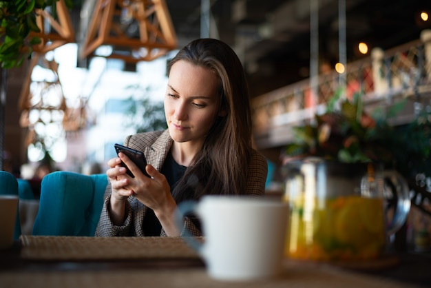 Woman uses a smartphone in his hands at the table in the restaurant Premium Photo