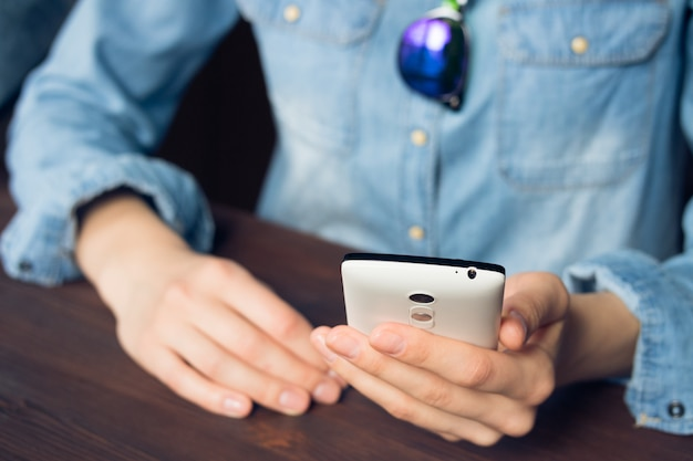 Woman uses a smartphone, she is dressed in a denim shirt and sunglasses Premium Photo