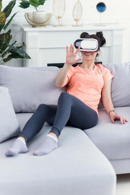女性はソファで自宅でvrゴーグルを使用します。未来のテクノロジー。 Premium写真