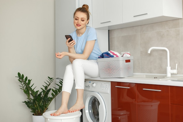 Woman uses a washing machine in the kitchen Free Photo