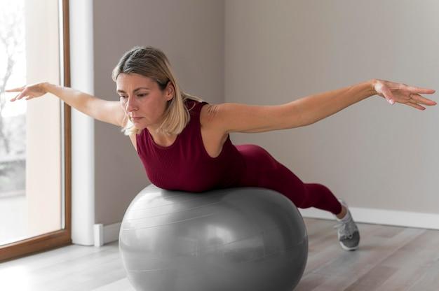 彼女のトレーニングにフィットネスボールを使用している女性 無料写真