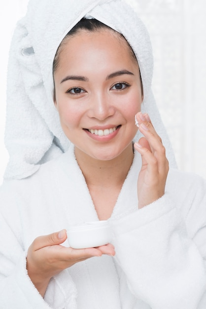 Woman using beauty cream in a spa Free Photo