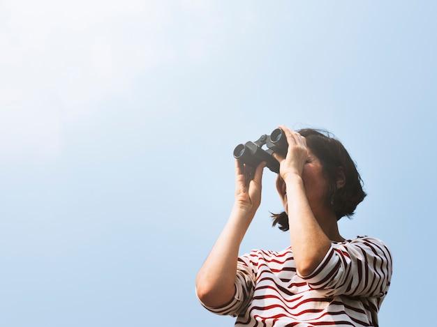 Woman using binocular explore searching Free Photo