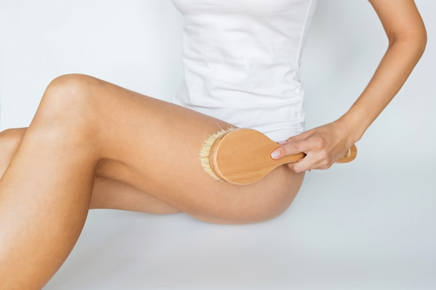 Woman using brush for massaging body on  white Premium Photo