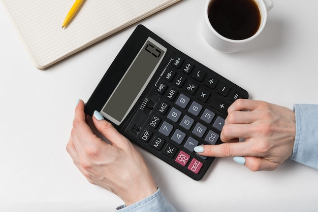 Premium Photo Woman Using Calculator Documents Cup Of Coffee And Calculator On A White