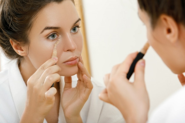 Woman using concealer Premium Photo