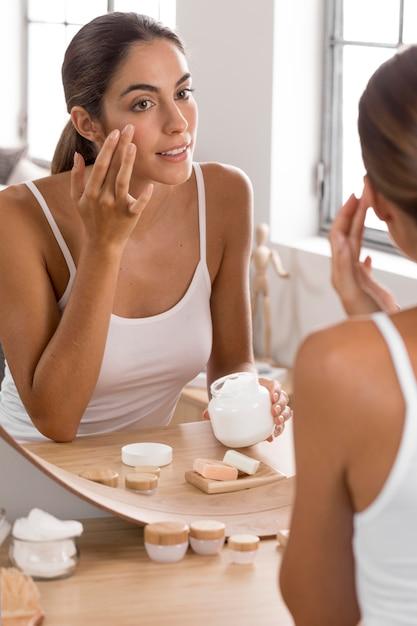Женщина, использующая концепцию ухода за собой крем Premium Фотографии
