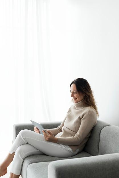 Donna che utilizza la tavoletta digitale su un divano Foto Gratuite