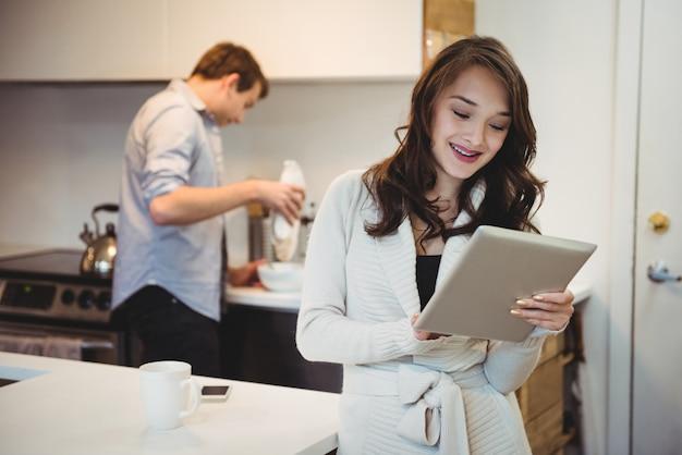 Женщина с помощью цифрового планшета, пока мужчина работает позади Бесплатные Фотографии