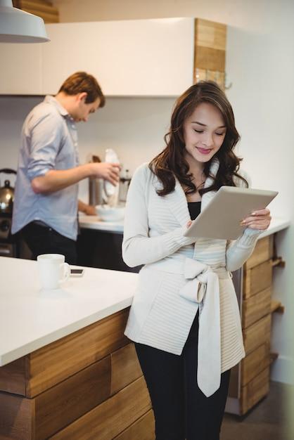 Женщина с помощью цифрового планшета, пока мужчина работает в фоновом режиме Бесплатные Фотографии