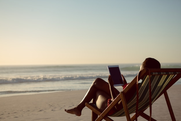 Woman using digital tablet while relaxing in a beach chair on the beach Free Photo