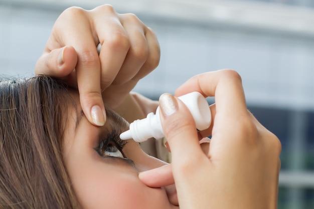 Woman using eye drop Premium Photo