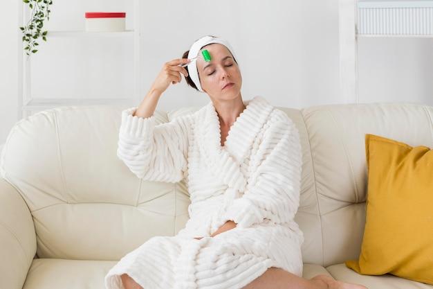 Женщина, используя ее повязку и массируя лицо, снимок Бесплатные Фотографии