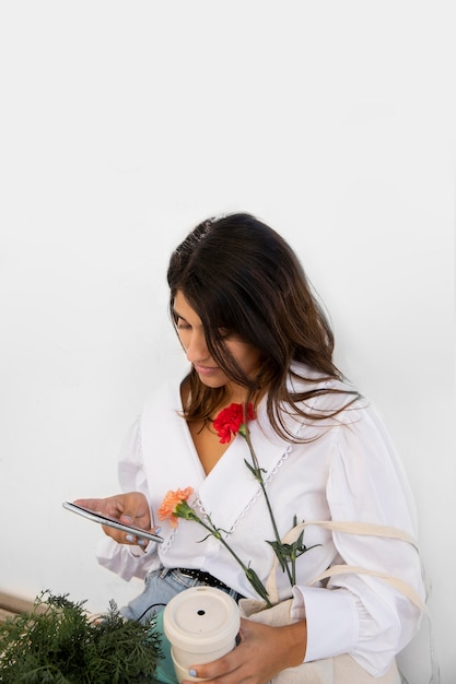 コーヒーを飲みながら屋外でスマートフォンを使用している女性 無料写真