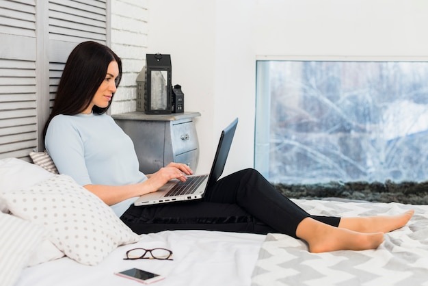 Woman using laptop on bed Free Photo