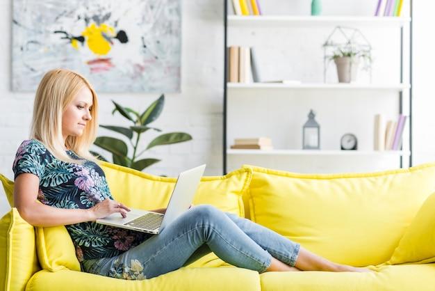 Woman using laptop sitting on sofa Free Photo