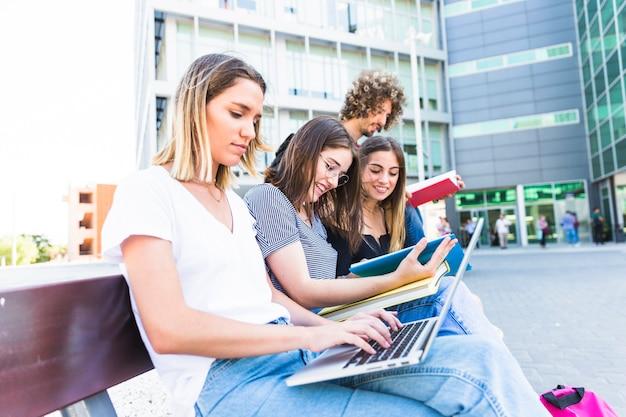 Woman using laptop for studies near friends Free Photo