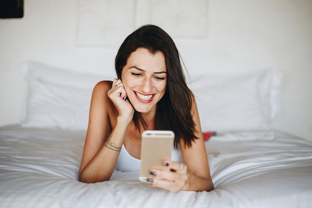 Woman using a mobile phone in bed Premium Photo