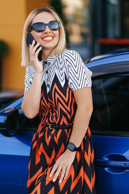 Женщина, использующая мобильный телефон, связь или онлайн-приложение, стоя возле автомобиля на городской улице или парковке, на открытом воздухе. каршеринг, прокат автомобилей Бесплатные Фотографии