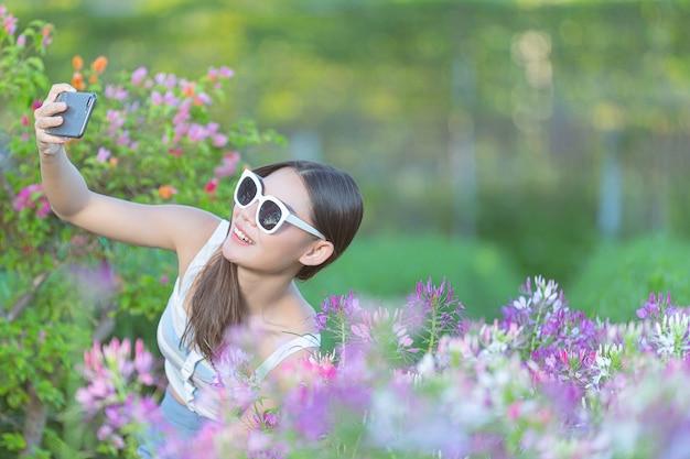 Donna che utilizza il telefono cellulare per scattare foto nel giardino fiorito. Foto Gratuite