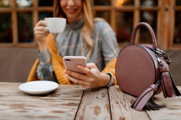Женщина с помощью мобильного телефона, текстовых сообщений и пить кофе. стильная сумка на столе. в сером платье и оранжевой клетке. наслаждаемся уютным утром в кафе. Бесплатные Фотографии