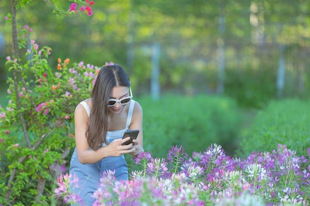 フラワーガーデンで写真を撮るために携帯電話を使用している女性。 無料写真
