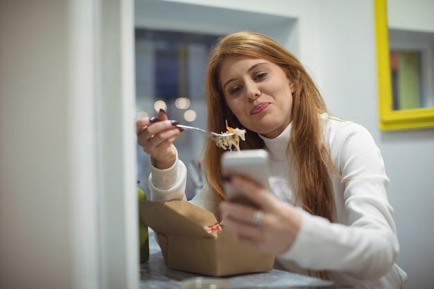 Женщина с помощью мобильного телефона во время еды Бесплатные Фотографии