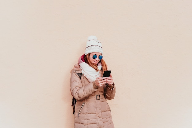 Woman using mobile phone on yellow wall. technology and winter concept Premium Photo
