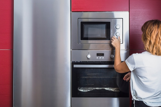 Woman using modern microwave oven Premium Photo