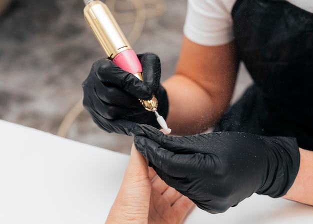 Woman using a nail file on client and wearing gloves Free Photo
