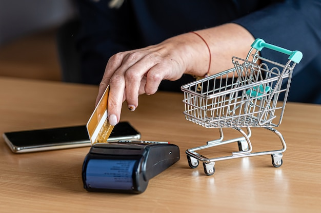 Woman using payment card terminal to shop online with credit card, credit card reader, finance concept Premium Photo