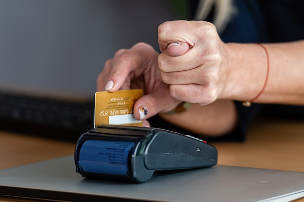 Женщина использует терминал для платежных карт для покупок в интернете с помощью кредитной карты и показывает другой рукой инжир Premium Фотографии