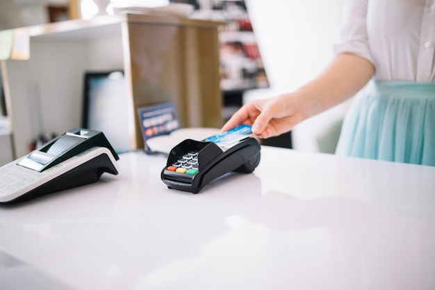 Woman using payment terminal on cashier desk Free Photo