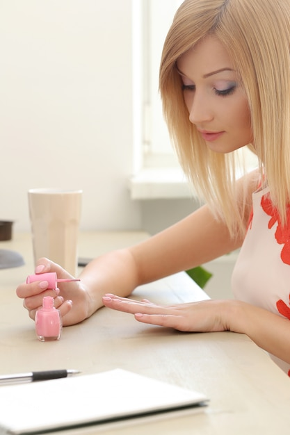 Woman using a pink lacquer Free Photo
