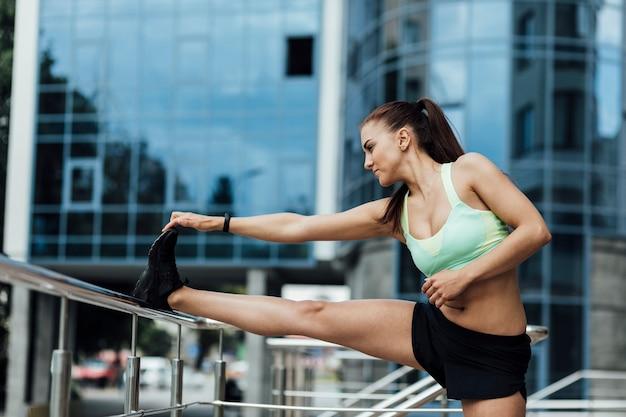 Woman using railing to stretch Free Photo