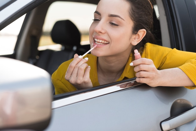 Woman using the rear-view mirror to apply lipstick Free Photo