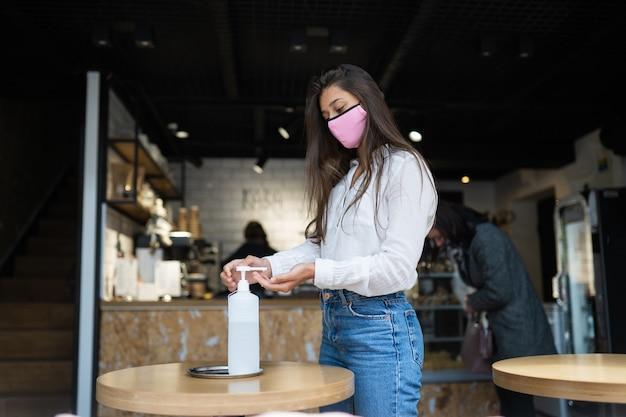 여자 살균 젤을 사용하여 카페에서 코로나 바이러스 바이러스의 손을 청소 무료 사진
