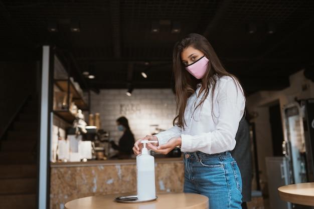 消毒ジェルを使用している女性は、カフェでコロナウイルスの手をきれいにします。 無料写真