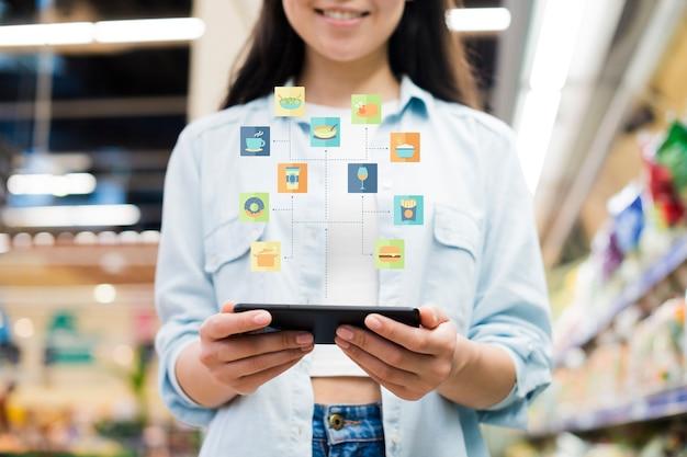 食料品店でスマートフォンを使用しての女性 Premium写真