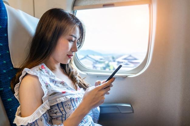 Женщина с помощью смартфона в поезде. Бесплатные Фотографии