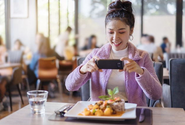 Woman using smartphone take photo of food before eating in restaurant Premium Photo