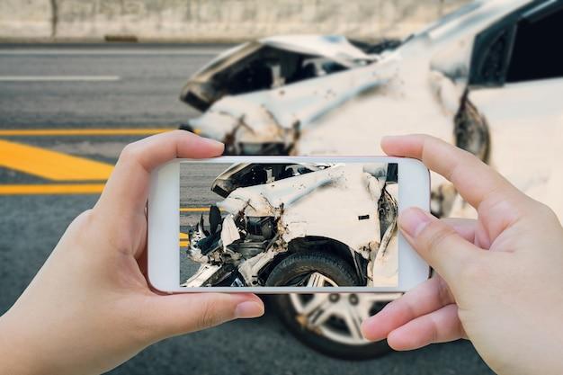 スマートフォンを使用して女性が路上での自動車事故の写真を撮る Premium写真