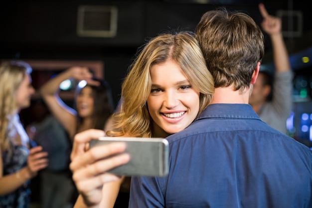 Woman using smartphone while hugging boyfriend Premium Photo